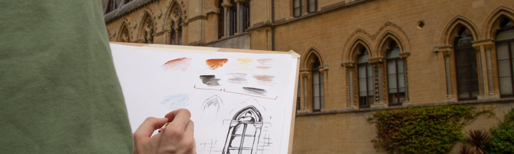 Sketching on an artboard in front of the Museum building