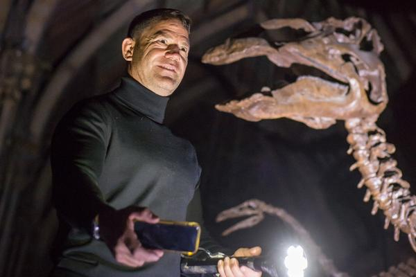 Man holding a flashlight and mobile phone in a dark space below the skeleton of a dinosaur